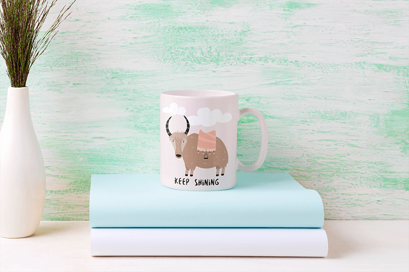 Mockup Of An 11 Oz Coffee Mug Placed On Top Of Some Books 43562 R El2