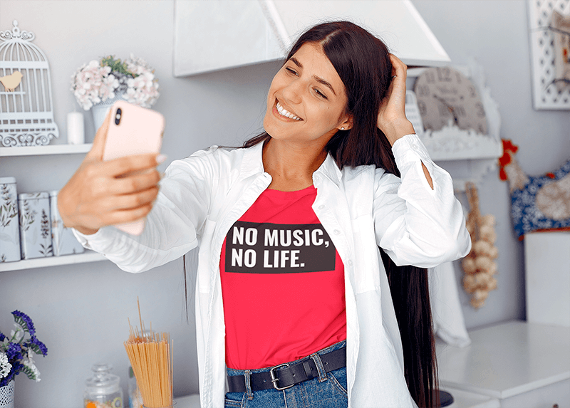 T Shirt Mockup Of A Young Woman Taking A Selfie At Home
