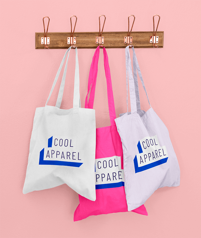 Mockup Of Three Customizable Tote Bags Hanging Against A Solid Color Wall