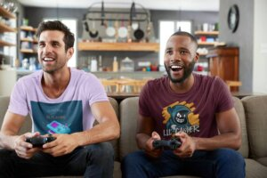 T Shirt Mockup Of Two Men Playing Video Games At Home