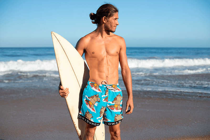 Swim Trunks Mockup Of A Surfer Man Holding His Board